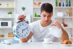 The man with alarm clock falling asleep at breakfast Royalty Free Stock Image