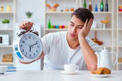The man with alarm clock falling asleep at breakfast Stock Photo
