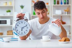 The man with alarm clock falling asleep at breakfast Stock Photos