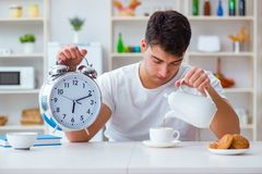 The man with alarm clock falling asleep at breakfast Royalty Free Stock Images
