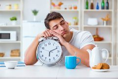 The man with alarm clock falling asleep at breakfast Royalty Free Stock Photos