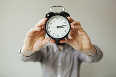 Man with alarm clock head in hands Royalty Free Stock Images