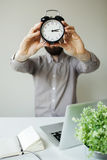 Man with alarm clock head in hands Stock Photos