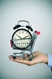 Man with an alarm clock in a shopping cart Royalty Free Stock Photos