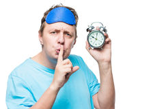 Man with an alarm clock showing a gesture quietly in a mask for Stock Photography