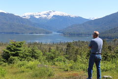 Man in Alaska Landscape. Alaska wilderness landscape with senior age Caucasian man with back to camera stock image