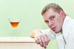 Man and alcohol. Handsome man sitting against glass of alcohol and looking at camera. Caucasian gay Royalty Free Stock Images