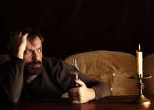 Man with alcohol. Afraid man with alcohol on the table Stock Photo