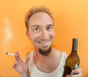 Man with alcohol and cigarette. Caucasian man holding a cigarette and a alcohol bottle with a big smile Royalty Free Stock Photo