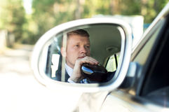 Man with alcohol driving a car Stock Image