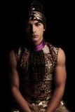 Man in alladin costume posing in dark studio background hands do Stock Photography