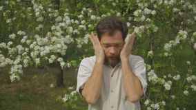 A man allergic to plants in a blooming garden. A man allergic to plants in a blooming garden stock video footage