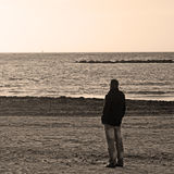 Man alone at the beach in sepia tone Stock Image