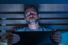 Man alone in bed playing cybersex using laptop computer watching sex movie late at night with lascivious pervert face. Young aroused man alone in bed playing stock photography