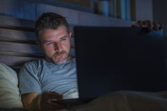 Man alone in bed playing cybersex using laptop computer watching sex movie late at night with lascivious pervert face stock photo