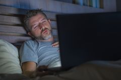 Man alone in bed playing cybersex using laptop computer watching sex movie late at night with lascivious pervert face. Young aroused man alone in bed playing stock images