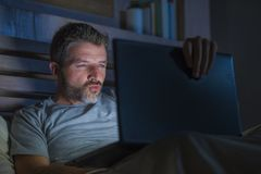 Man alone in bed playing cybersex using laptop computer watching sex movie late at night with lascivious pervert face. Young aroused man alone in bed playing royalty free stock image