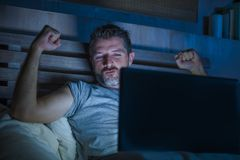 Man alone in bed playing cybersex using laptop computer watching sex movie late at night with lascivious pervert face. Young aroused man alone in bed playing royalty free stock photos
