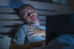 Man alone in bed playing cybersex using laptop computer watching sex movie late at night with lascivious pervert face. Young aroused man alone in bed playing royalty free stock photography