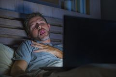 Man alone in bed playing cybersex using laptop computer watching sex movie late at night with lascivious pervert face. Young aroused man alone in bed playing royalty free stock photo