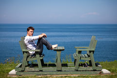 Young man sitting on the bench Royalty Free Stock Photos