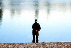 Man Alone on Coast. Man standing alone on rocky shore beside calm water stock photos