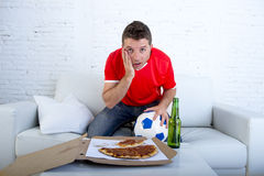 Man alone holding ball with beer and pizza in stress wearing team jersey watching football game on tv Royalty Free Stock Photo