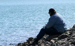 Man Alone at the Lake. A lonely, solitary man sits on the rocks next to the lake with fishing poles Royalty Free Stock Photos