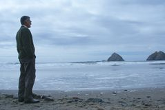 Man Alone Meditating or Thinking. Man standing alone on the beach looking out at the ocean on a cold cloudy day in Oceanside, Oregon, United States with Three Stock Photos