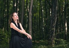 Man alone with nature forest. Portrait of a young woman in a black dress sitting in the woods. Listen to the sounds of nature Stock Images