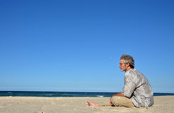 A man alone on white sandy beach. Older mature man sitting alone on a beautiful white sandy beach looking out across the beautiful blue ocean. Photograph taken Stock Photography