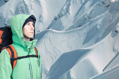 Man alpinist looks up against a winter mountain landscape. Stock Image