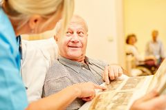 Man with Alzheimer`s looks at photo album. Old men with Alzheimer`s looks at photo album supervised by a caregiver stock photos