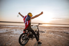 Man in american flag cape with hands up in air Stock Photos
