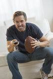 Man With American Football Watching TV Royalty Free Stock Image