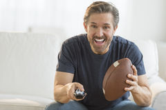 Man With American Football Watching TV. Excited mature man with American football watching TV on sofa Royalty Free Stock Images