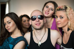 Man with an amulet and four girls. Bald men with an amulet in the form of fang and four beautiful girls stock photos