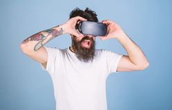Man with amused look and open mouth enjoying 3D experience. Bearded man with tattoo watching 360 video in VR goggles. Virtual reality concept. Hipster with royalty free stock photo