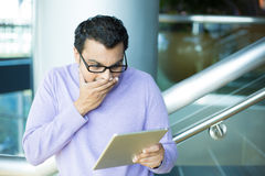 Man amused by what he sees on tablet Royalty Free Stock Photos