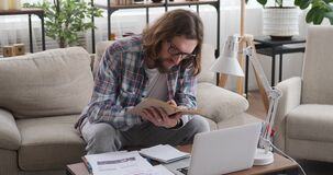 Man analysing documents and reading book at home office