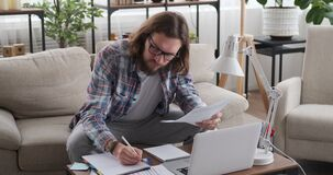 Man analysing documents and writing notes at home office