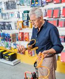 Man Analyzing Air Compressor Hose In Shop. Senior man analyzing air compressor hose in hardware shop Stock Image