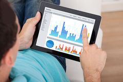 Man Analyzing Graphs On Digital Tablet Stock Photography