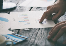 Man analyzing sales reports on a wooden table. Close up Royalty Free Stock Photos