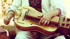 Man in ancient clothes playing on the hurdy-gurdy stock video