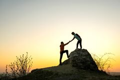 Free Man And Woman Hikers Helping Each Other To Climb A Big Stone At Sunset In Mountains. Couple Climbing On A High Rock In Evening Stock Image - 183393481