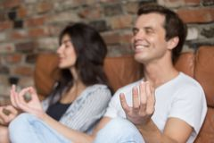 Free Man And Woman Meditate Sitting On Couch At Home Royalty Free Stock Photo - 128620165