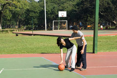 Man And Woman Playing Basketball - Horizontal Stock Photo