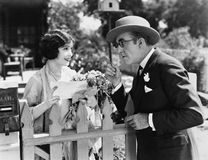 Man And Woman Talking Over A Picket Fence Stock Images