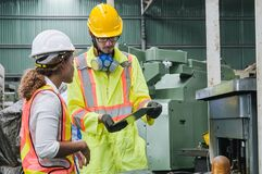 Free Man And Women Industrial Engineers Wearing Safety Uniform And Hard Hats With Tablet Working Heavy Industry. Royalty Free Stock Photography - 190296797
